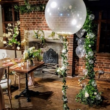 Giant clear balloon with a rose garland and petals, looks utterly gorgeous.  Scattered small clear balloons floating on clear wire and and ivy, white rose and clear balloon organic arch, something new I tried, I thought it turned out well!